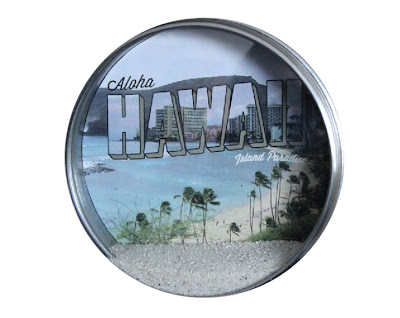 round tin with hawaian image and sand displayed inside