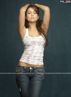 Amrita Arora's armpits show in a white vest with her arms in the air