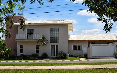 A elevação lateral da casa conta com um grande painel de blocos de vidro sobre uma porta de correr que atua como acesso secundário da edificação.