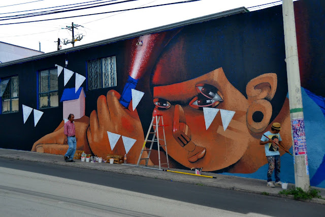 street artist jade working on a new mural