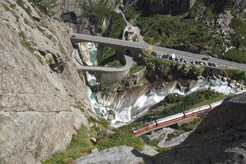 This is the reward for the adventurous ascent through the Devil's Wall. Schöllenen Gorge, old and new Devils Bridge and the Matterhorn-Gotthard Railway, Switzerland.