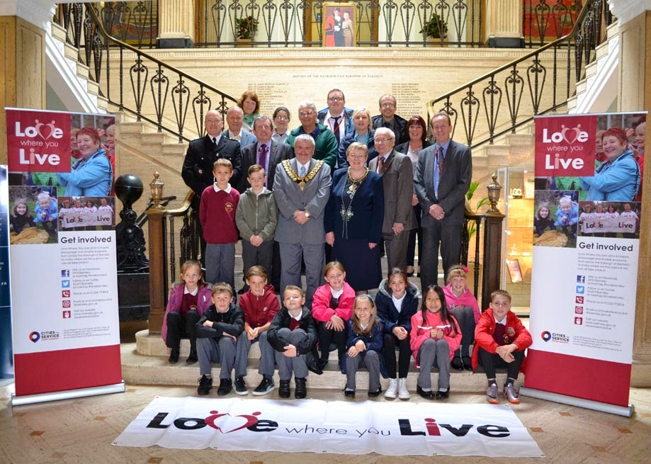 "Children, the mayor and mayoress and various helpers standing on the steps inside Barnsley Town Hall.  There is a banner on the floor reading ""Love Where You Live""."