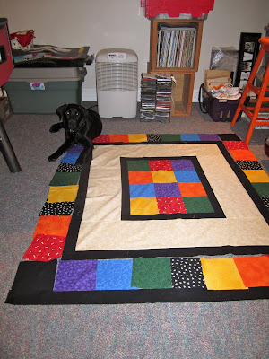Black lab puppy Romero is lying at the top left corner of the partially sewn together quilt that is lying on the floor. The centre of the quilt is a rectangle of 4 squares by 3 squares of red, orange, yellow, green, blue, and purple patterned fabric. Around that is a thin border of plain black. Around that is a thick border of cream fabric with white bones and light brown pawprints on it. Around the cream is another thin black border. Laid out around the edge of the outside black border is another row of coloured squares along with a few plain black squares and a few black squares with white paw prints. These squares are not yet sewn together as we were just in the middle of rearranging them to determine the best pattern. Romero is attempting to help out by laying on top of some of the fabric squares!
