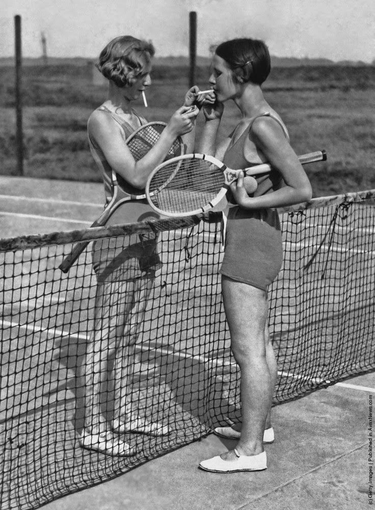 Two women lighting cigarettes on a tennis court in essex england