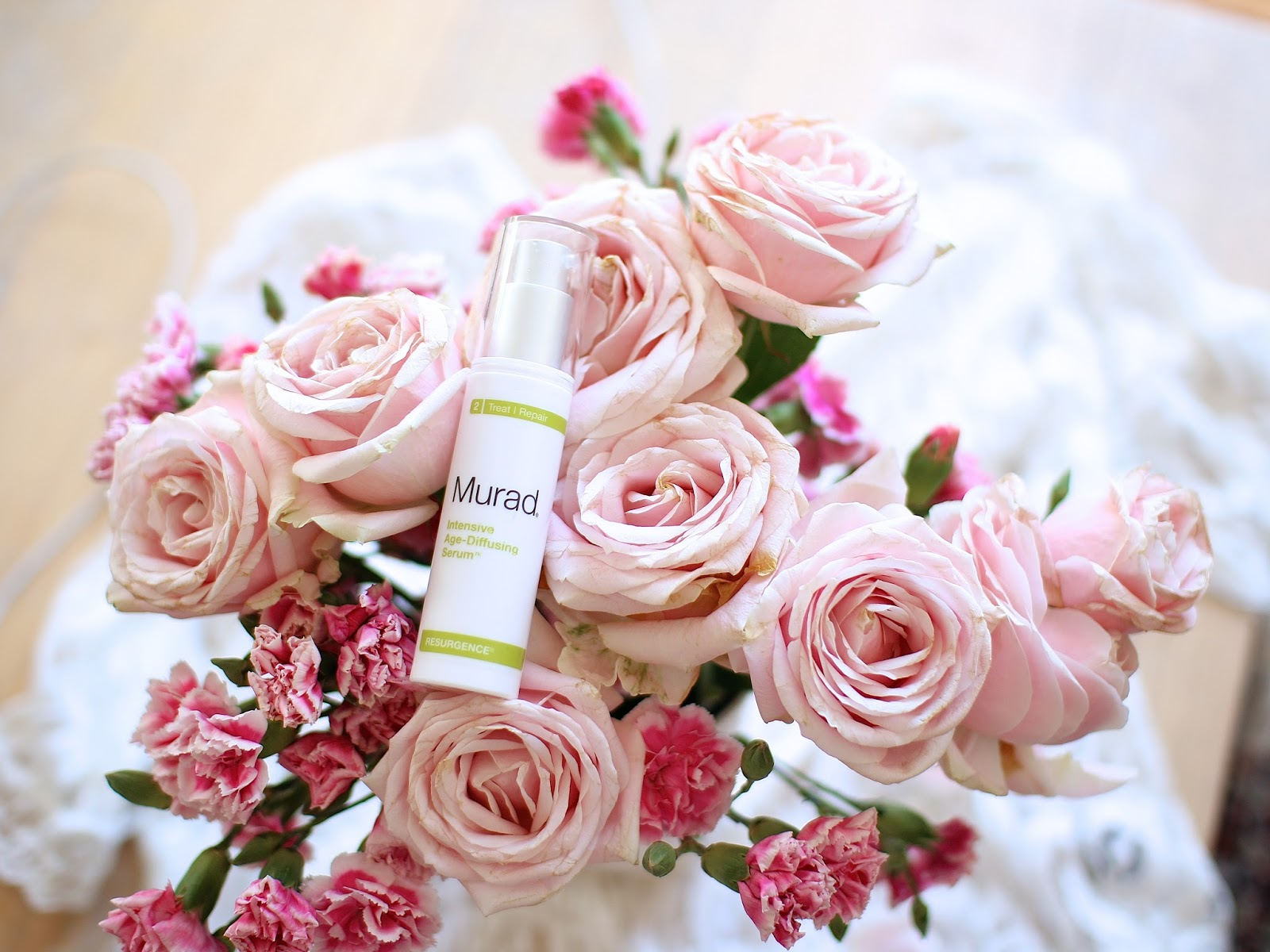 beautiful blush toned roses from london flower market shown with a moisturizing skincare product
