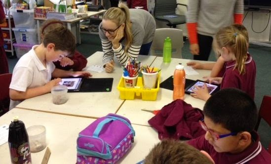 children working on iPads in pairs, communicating with each other about their work