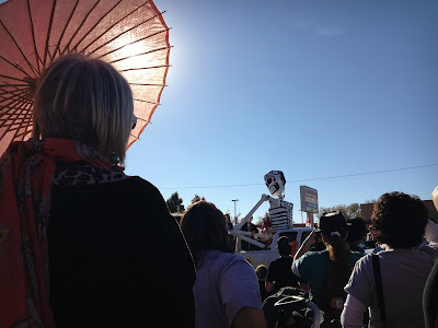 Woman with parasol watching the South Valley Marigold Parade in Albuquerque, New Mexico during a Dia de los Muertos celebration.