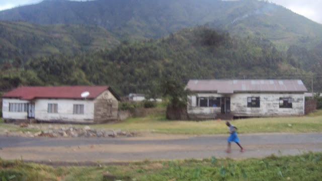 Boy running alongside derelict houses in Kilembe.
