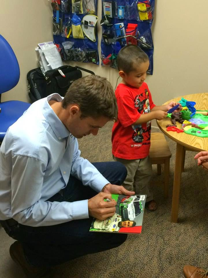 David signs an autograph for a child at the hospital.