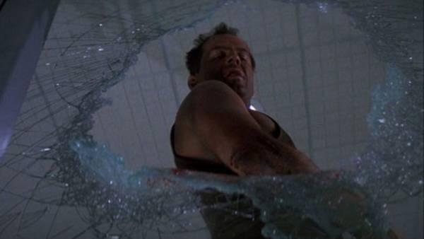 John McClane guarda da un buco nel vetro fatto da lui