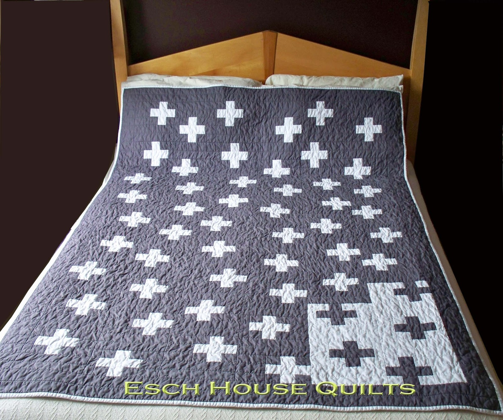 Grey Quilt with White Cross Pattern Laying on Bed