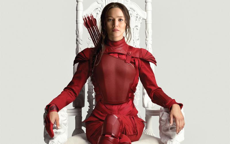 Na imagem de capa: Katniss Everdeen usando uma armadura inteiramente vermelha está sentada em uma cadeira branca grande que parece um trono.