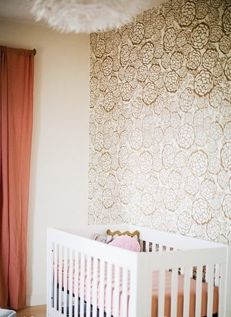 feature wall gold wallpaper white crib baby room nursery peach accents