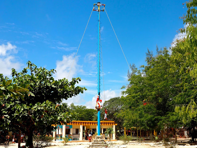 Men swinging upside down around a pole, in a prayer ceremony, outside Tulum ruins, Mexico
