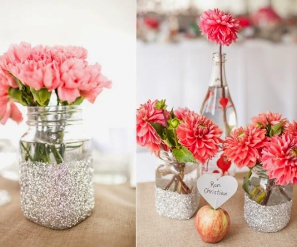 Para la primera inspiración de centros de mesa con flores tan solo necesitas unos tarros y botellas de cristal. Lo puedes adornar con polvo de brillantina,