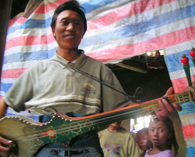 Tibetan man playing a dramyin.