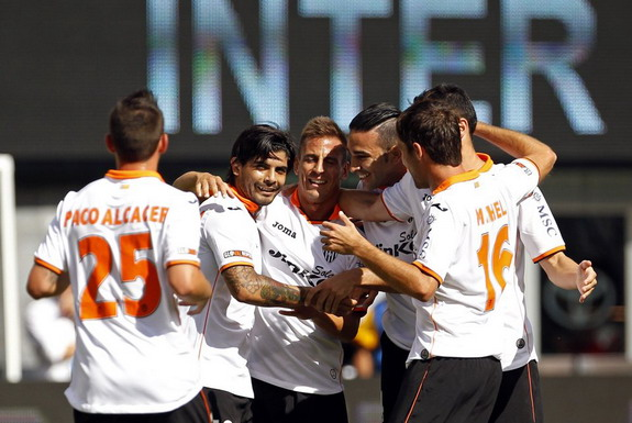 Éver Banega is congratulated by Valencia teammates after scoring a goal against Inter Milan