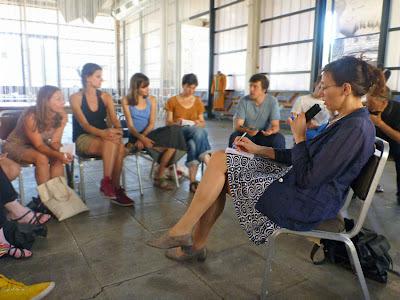 Dolmetscherin mit Mikrofon inmitten einer diskutierenden Gruppe, die auf Stühlen im Kreis sitzt.