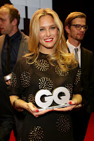 Bar Rafaeli wearing a seee through black shirt and holding a GQ award