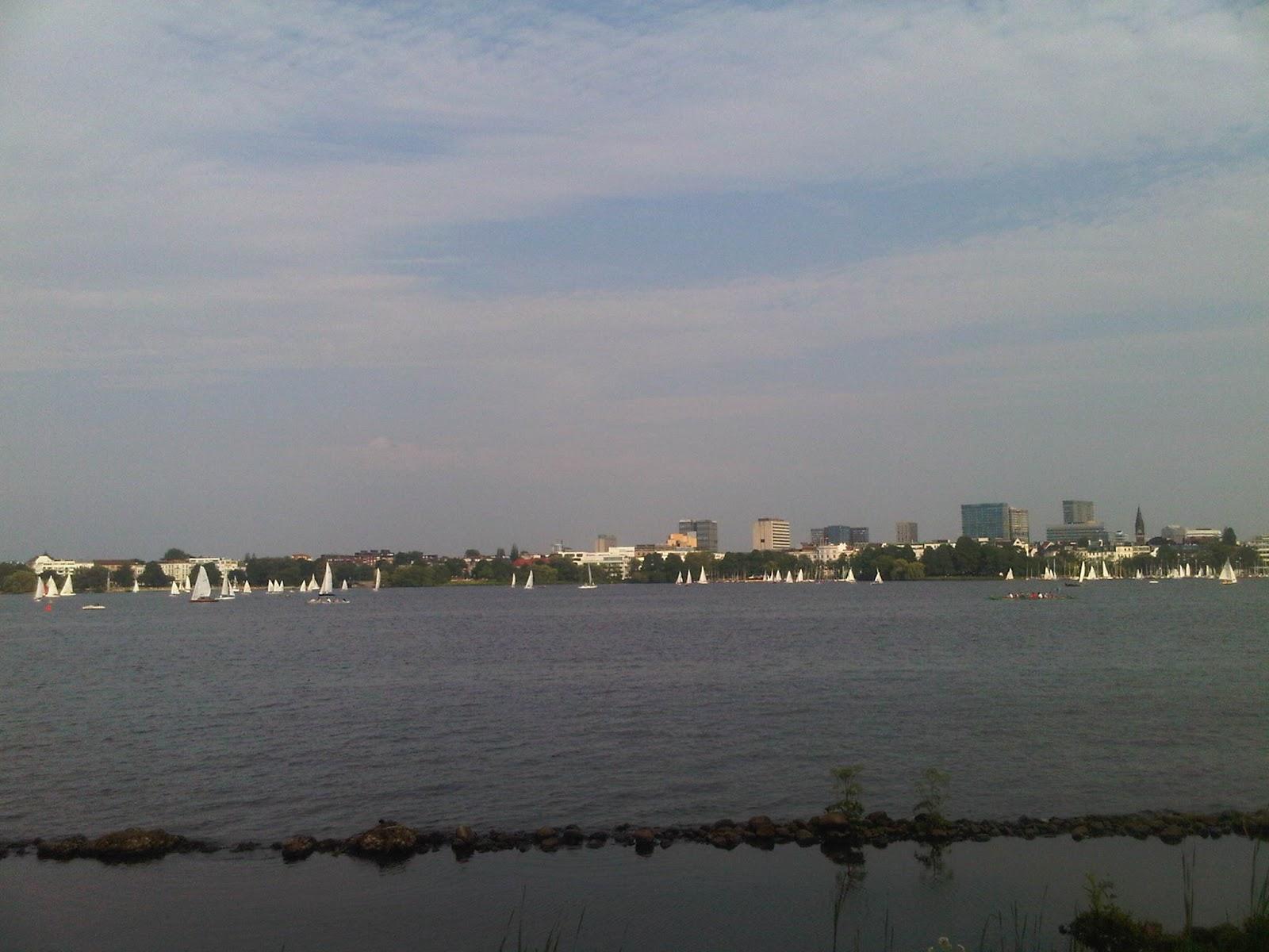 Außenalster mit Segelschiffen, Wasser, Himmel mit Wolken, Hochhäuser im Hintergrund.