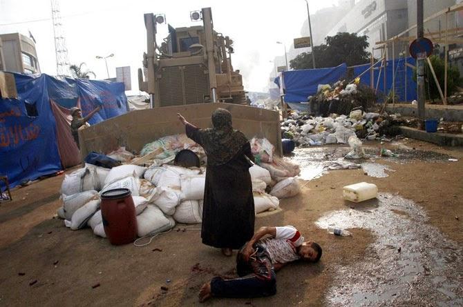 Женщина защищает раненого демонстранта от военного бульдозера в Египте, 2013 год.