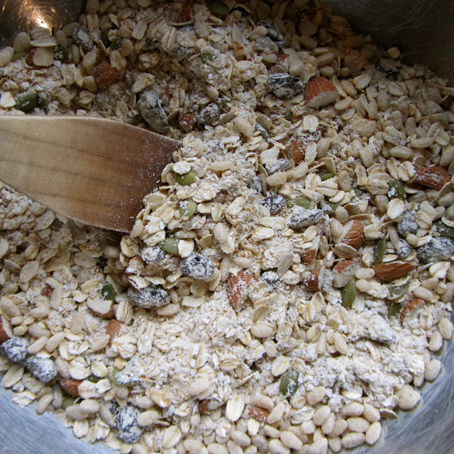 all muesli ingredients in a bowl mixed with a wooden spoon