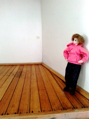 Modern dolls' house miniature doll standing on a wooden floor and leaning against a white wall.
