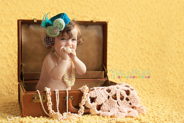 Little girl sitiing in a vintage suitcase with a teal pill box hat and pearls in Hendersonville, NC.