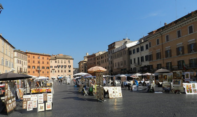 There are many artist booths set up in the Piazza