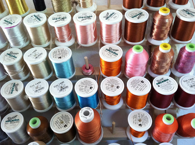 Wall of colored thread spools at Hipsters for Sisters studio