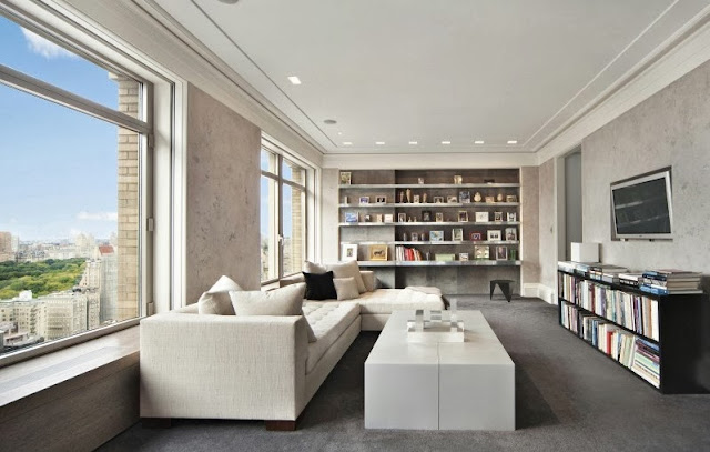 Media room in a NYC penthouse with white sectional sofa and ottoman