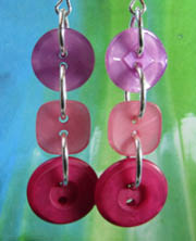 Flattering pink drop dangle earrings have 3 detailed buttons linked in long strand with silver loops