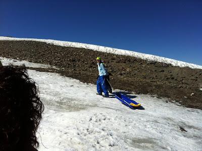 En la imagen se ve a uno de nuestros alumnos tirando del trineo para subirlo hasta lo alto de la loma.