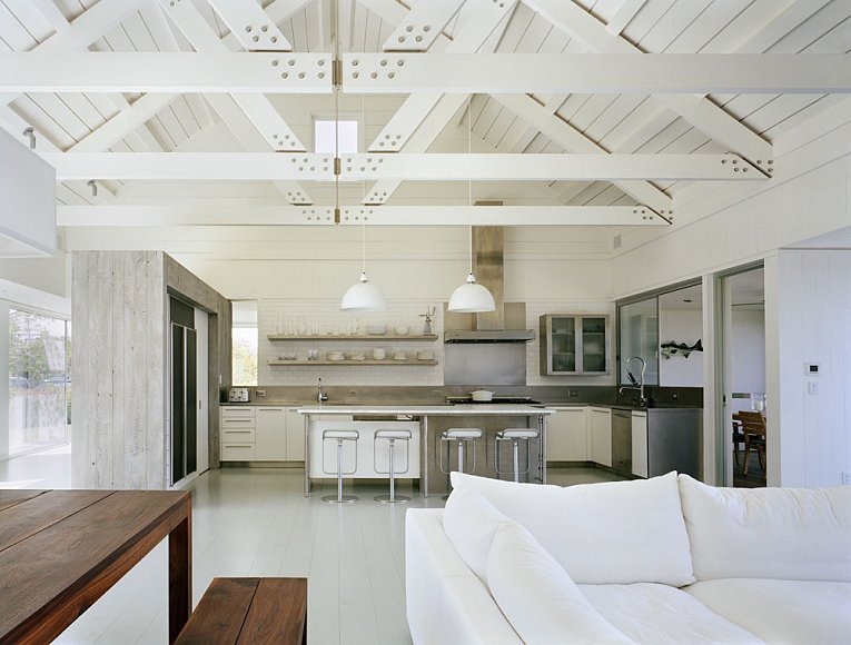Open living kitchen in a Montauk on Long Island lake house with high ceiling, exposed beams, silver barstools. In the foreground there is a wood dining room table with bench seating and a white sectional sofa