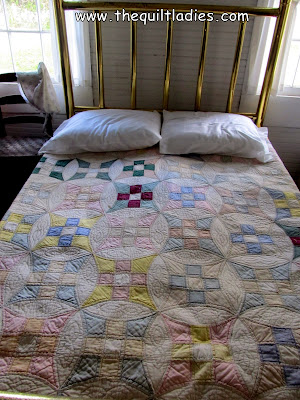 scrap quilt on old iron bed