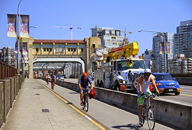 Riders enjoy a newly fortified bike lane on a bridge in downtown Vancouver, British Columbia. (Credit: Danielle Griscti, courtesy of Flickr.) Click to Enlarge.