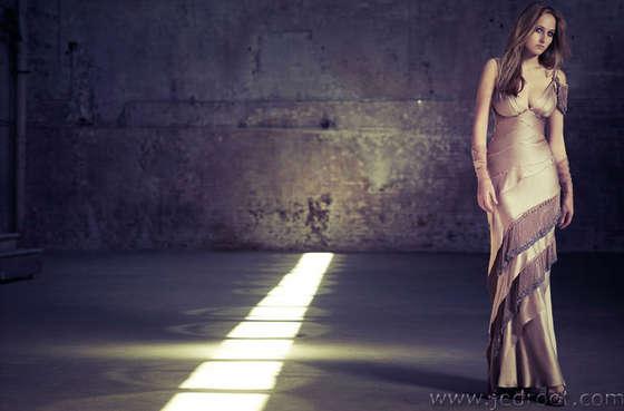 Leelee Sobieski posing in a dress beside ray of light