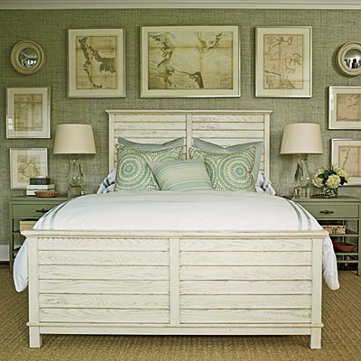 Master bedroom with sea grass aqua wallpaper, framed nautical prints on the wall behind the large wood bed with two matching night stands and a sea grass area rug on a wood floor