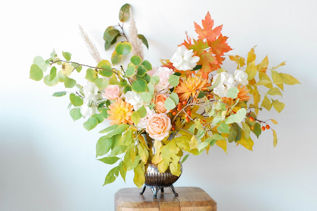 foraged fall aspen and maple branches with peach and white garden roses, dahlias, berries and grasses arranged in an antique silver pitcher
