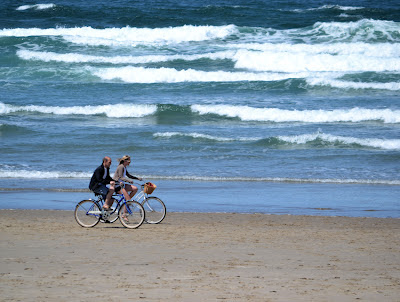 photo of couple biking on Rockaway Beach by Nanzy Zavada