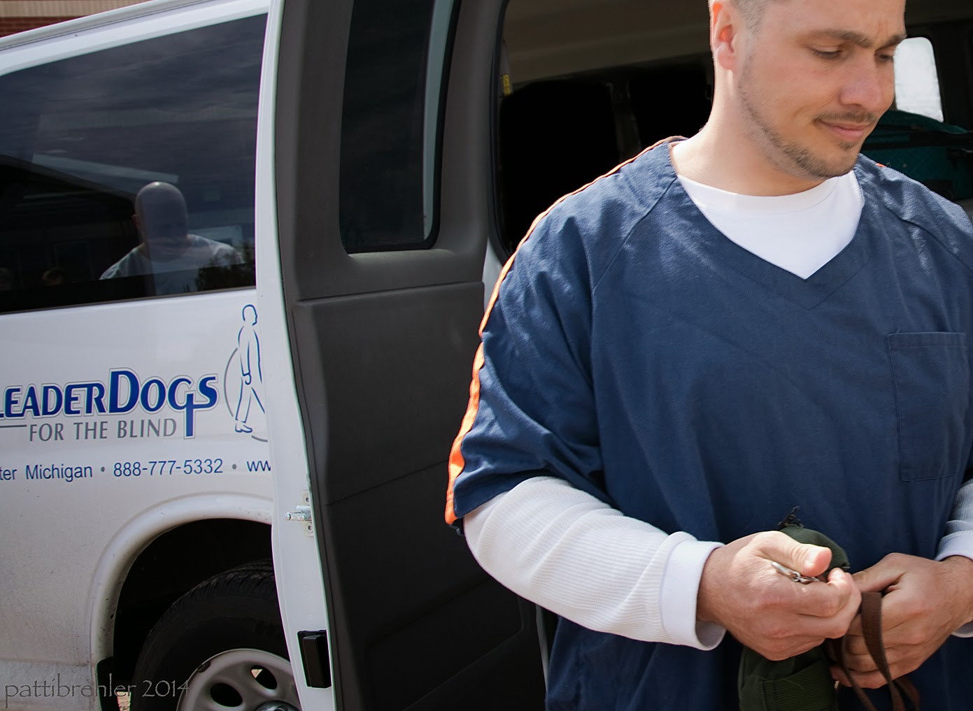 A man waring a blue shirt with a long sleeved white shirt under it is walking away from the Leader Dog white van, he is looking down and is holding a green treat bag and a leash in his hands, which are by his waist.