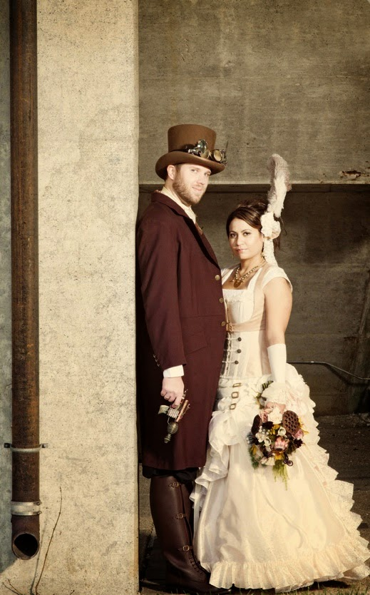 Steampunk wedding couple wedding dress feather top hat gun suit