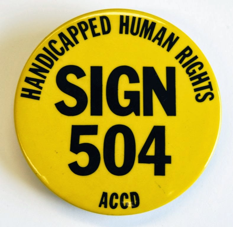 "Sign 504 Button - 1977. Bright yellow button with bold type that says: ""SIGN 504"" big in middle. ""Handicapped Human Rights"" at top, and ""ACCD"" at bottom"