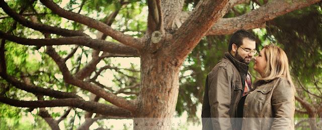 pareja se mira junto a las ramas de un arbol