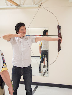 Hwan shooting a bow and arrow.