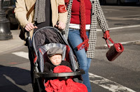 Photo of couple pushing  child in stroller across crosswalk, using curb cuts
