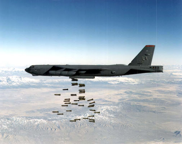 A B-52H Stratofortress drops a load of M-117 750-pound bombs.