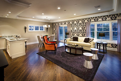 a scheme of the living area includes the kitchen-dining and lounge area with accent wallpaper and purple carpet