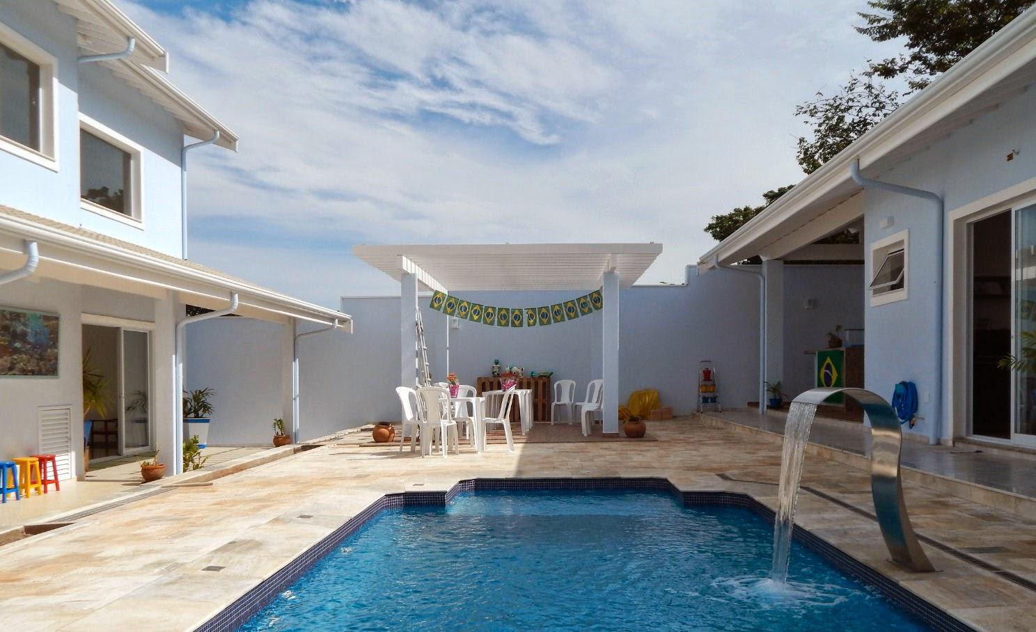 O pergolado diante da piscina com cascata é adornado com bandeiras do Brasil, em clima de Copa do Mundo. O céu de brigadeiro faz composição com a área de lazer.