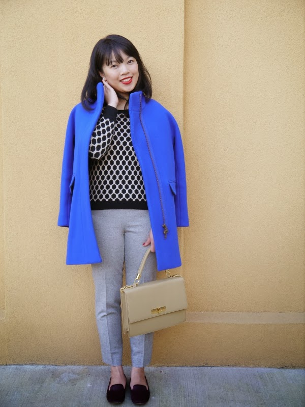Cobalt blue cocoon coat worn with graphic black-and-white sweater, grey ankle trousers, burgundy pony hair smoking slippers, and a structured top-handle bag.